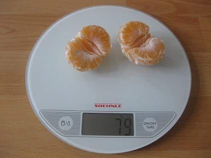 geschälte Mandarinenhälften auf der Waage
